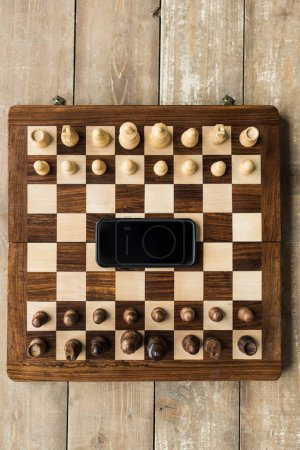 Top view of chess board with smartphone and chess pieces on wooden surface