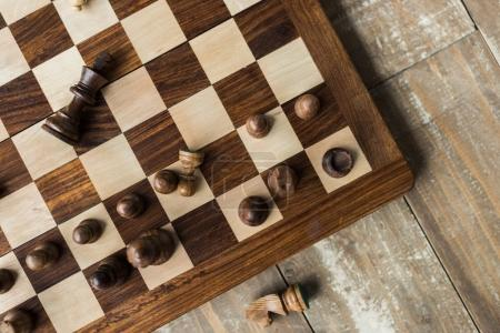 Top view of chess board with scattered black chess pieces on rusitc wooden surface