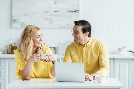 Joli couple avec café en regardant l'autre et assis devant l'ordinateur portable sur la table de la cuisine