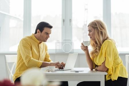 Blonde woman drinking coffee and looking at thoughtful man working on laptop