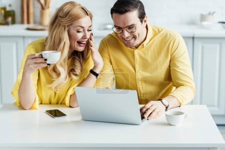 Cheerful man and woman drinking coffee and looking at laptop screen