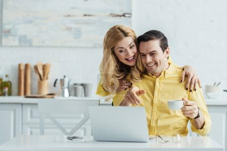 woman hugging man who looking at laptop screen at home