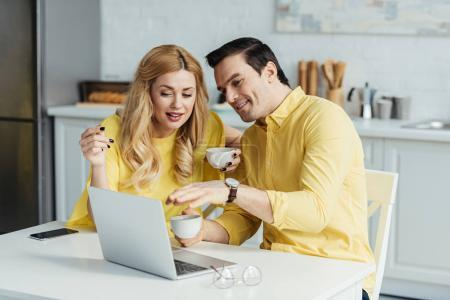 Man and woman drinking coffee and looking at laptop screen by kitchen table