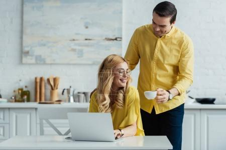 Attentive boyfriend giving coffee to woman working by laptop
