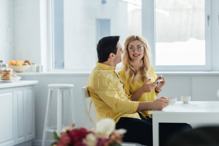 Man and woman with smartphone drinking coffee and talking by kitchen table