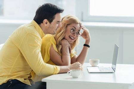 Man and woman drinking coffee and looking at laptop screen