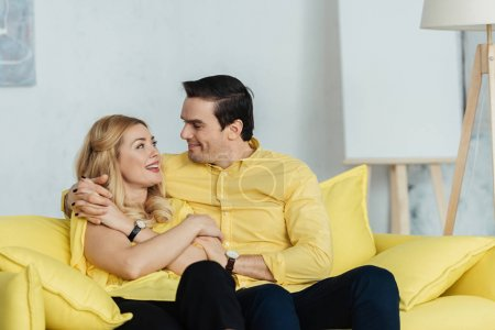Photo for Pretty couple looking at each other and sitting on yellow sofa - Royalty Free Image