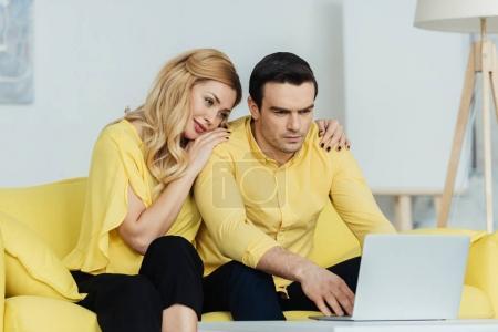 Blonde woman hugging her boyfriend working on laptop