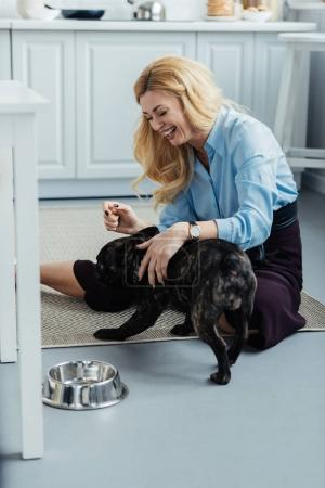 Smiling blonde woman playing with frenchie dog on kitchen floor