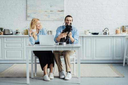 Man and woman drinking coffee and playing with french bulldog on kitchen table with laptop