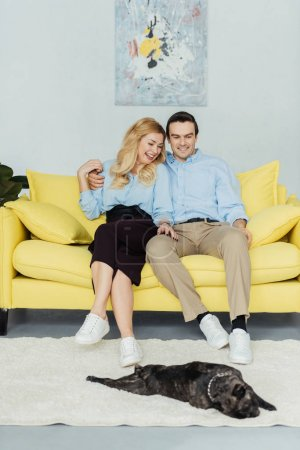 Embracing man and woman sitting on yellow sofa by frenchie puppy on floor