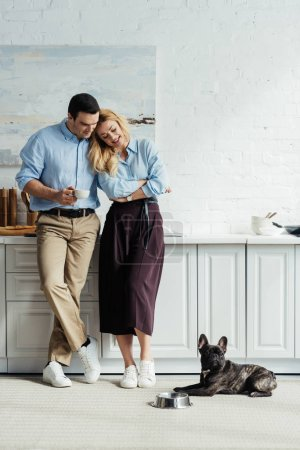 Couple drinking coffee and looking at french bulldog on kitchen