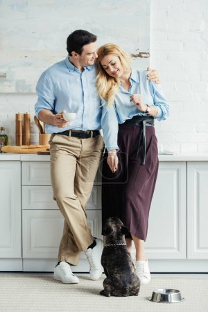 Man and woman drinking coffee by their dog pet on kitchen