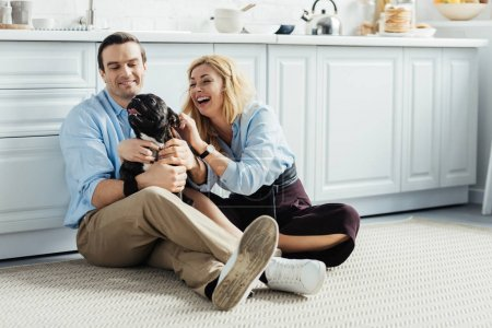 Man and woman playing with their dog on kitchen floor