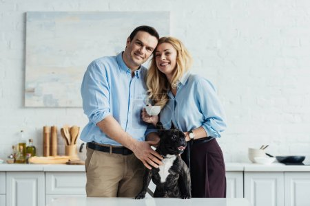Smiling couple stroking their frenchie dog on kitchen table