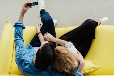 overhead view of embracing man and woman sitting on sofa and taking selfie