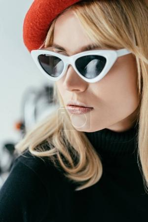 Stylish pretty woman in red beret and sunglasses