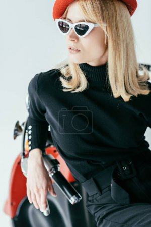 Elegant blonde girl in black clothes posing by vintage scooter isolated on grey