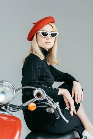 Photo pour Élégante fille blonde en vêtements noirs posant par scooter vintage isolé sur gris - image libre de droit