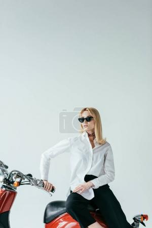 Stylish blonde girl sitting on retro scooter isolated on white