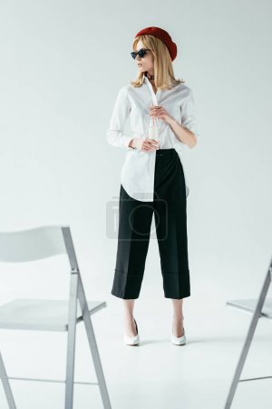 Stylish pretty woman in black and white clothes standing in front of chairs