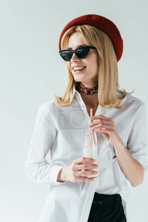 Attractive young woman in sunglasses drinking milk isolated on grey
