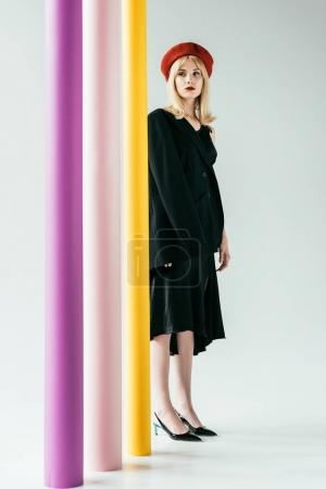 Stylish blonde girl in black dress posing by colorful pillars