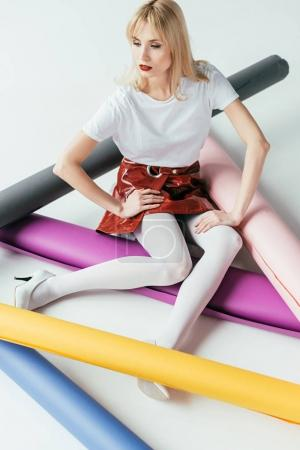 Attractive young woman posing among colorful paper rolls