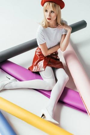 Elegant blonde girl posing among colorful paper rolls