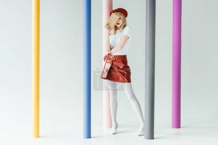 Photo pour Jolie fille blonde tenant livre et posant par des piliers colorés - image libre de droit
