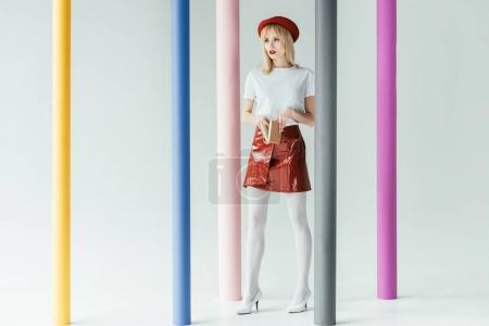 Stylish pretty woman holding book and posing by colorful pillars