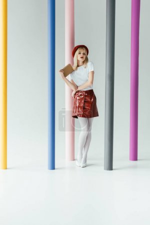 Attractive young woman holding book and posing by colorful pillars