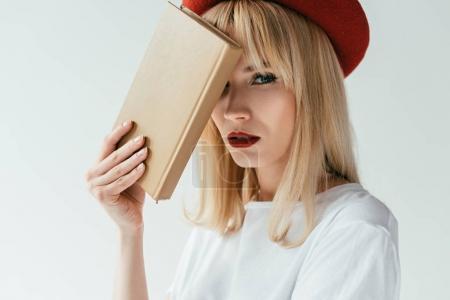 Photo pour Fille blonde à la mode avec lèvres rouges tenant livre isolé sur gris - image libre de droit