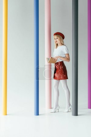 Stylish pretty woman posing by colorful pillars