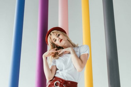 Attractive young woman in red and white clothes by colorful columns isolated on grey