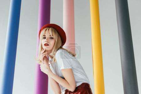 Pretty blonde girl in red and white clothes by colorful columns