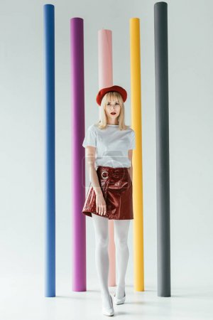 Stylish pretty woman in vintage style clothes in front of colorful columns