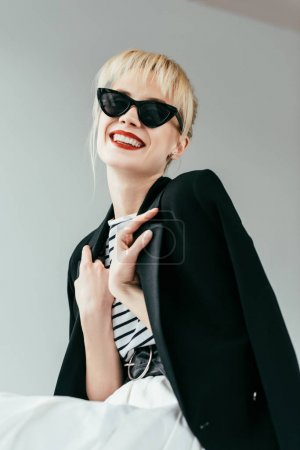 Stylish pretty woman in sunglasses with red lips isolated on grey