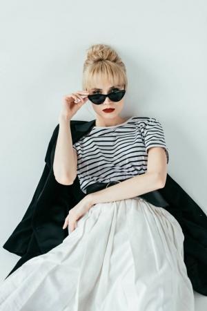 Photo pour Jolie jeune femme en noir et blanc vêtements et lunettes de soleil - image libre de droit