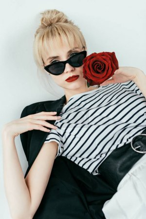 Stylish pretty woman posing with red rose