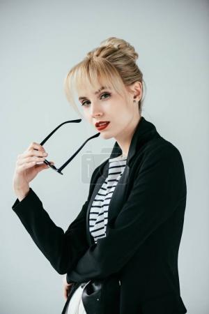 Photo pour Souriant fille blonde tenant des lunettes de soleil rétro isolé sur gris - image libre de droit