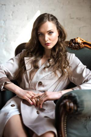 attractive woman in beige trench coat sitting in armchair