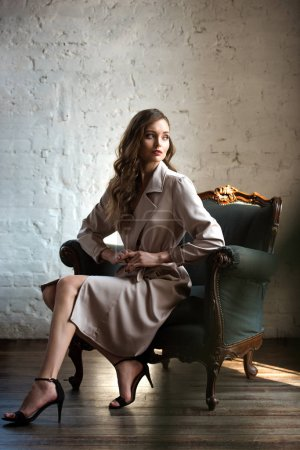 elegant woman in classic trench coat posing in armchair