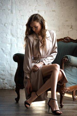 seductive woman in beige trench coat sitting in armchair