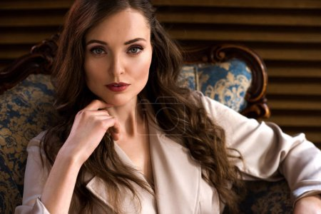 Photo for Brunette woman with long hair in beige trench coat looking at camera - Royalty Free Image