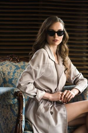 Photo for Beautiful woman in sunglasses and trench coat posing in armchair - Royalty Free Image