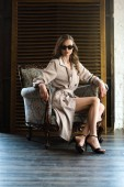 sensual woman in sunglasses and classic trench coat posing in armchair