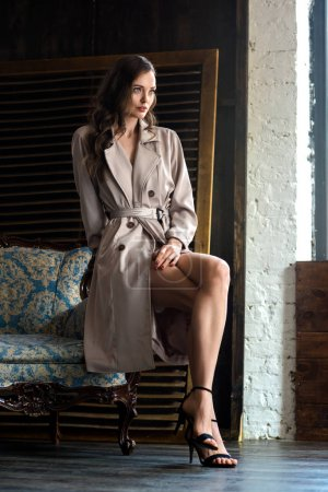 Photo for Elegant woman in trench coat sitting on armchair - Royalty Free Image