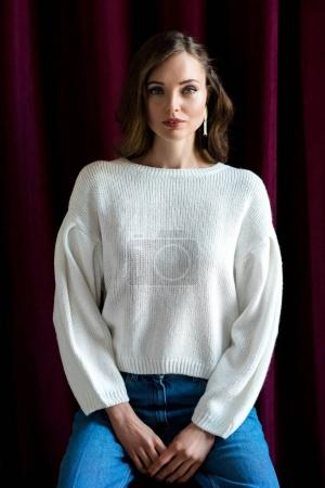 portrait of beautiful young brunette woman in white sweater and jeans looking at camera