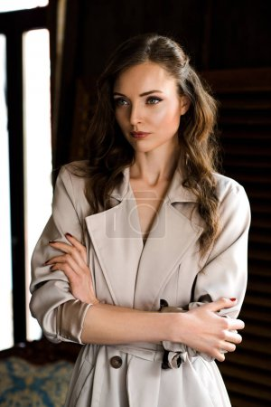 Photo for Beautiful woman in trendy trench coat with crossed arms - Royalty Free Image
